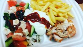 Гирос на тарелке с картофелем фри и Греческим салатом